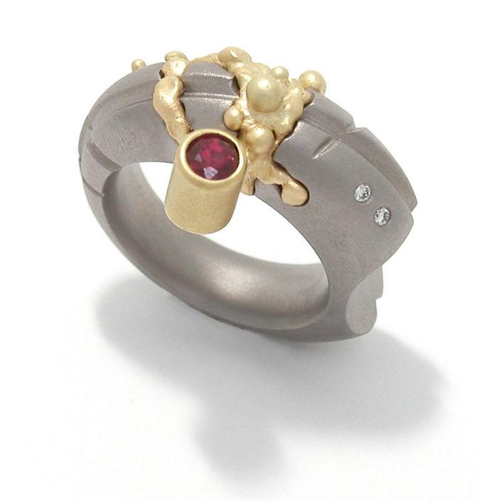 Ring 'Lava Ruby', titanium, geelgoud (in 'lava-techniek'), bezet met een robijn en twee diamanten.